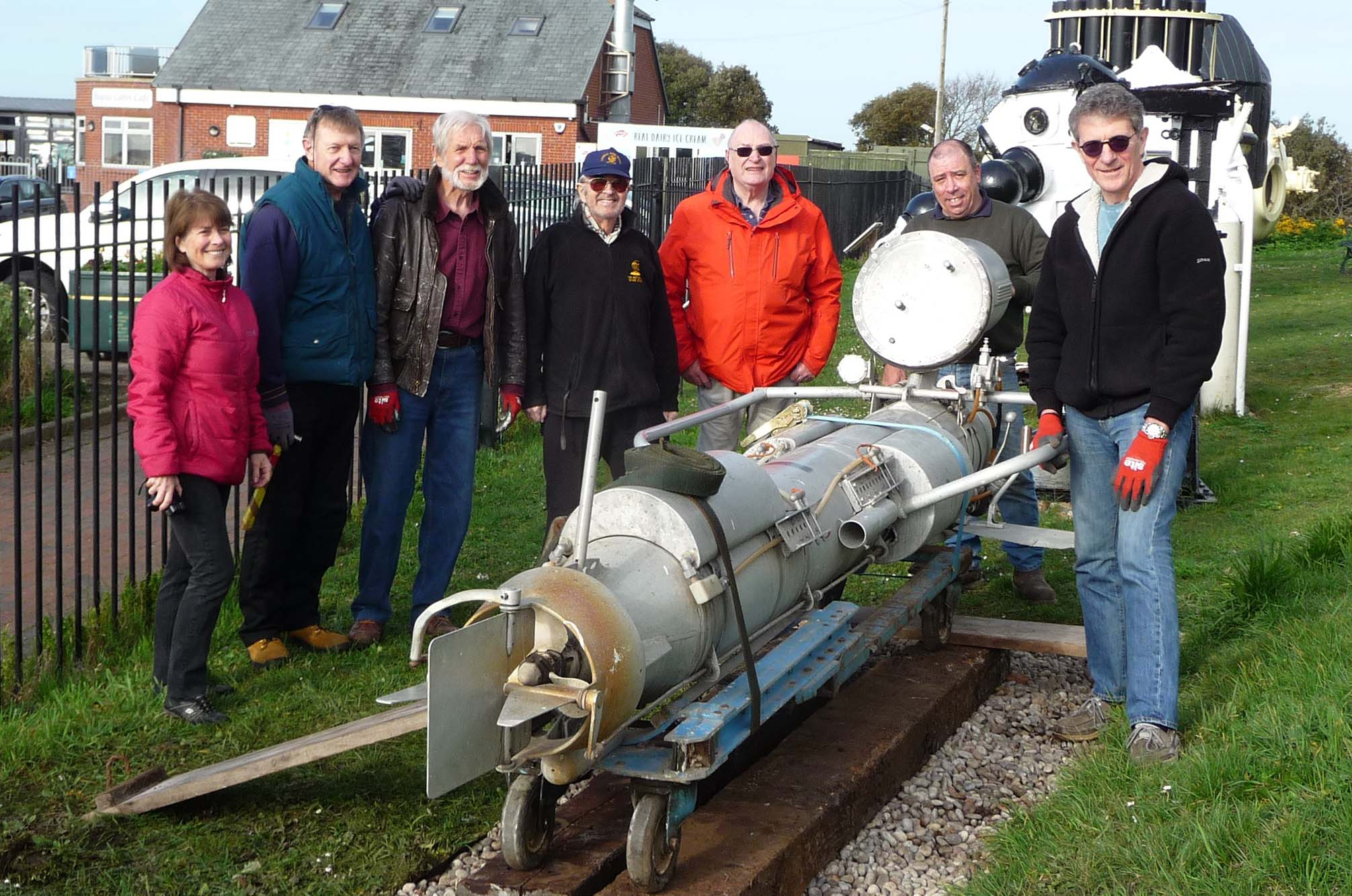 Group of seven museum volunteers standing behind the torpedo-shaped swimmer delivery vehicle in the outside exhibit area of the museum.